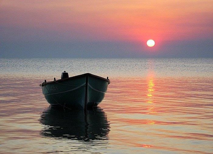в море при штиле плывут навстречу друг другу мальчик и спасатель на лодке